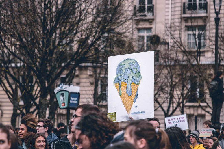 Plakat, auf dem eine schmelzende Weltkugel auf einer Eiswaffel zu sehen ist. Foto: Unsplash/Harrison Moore